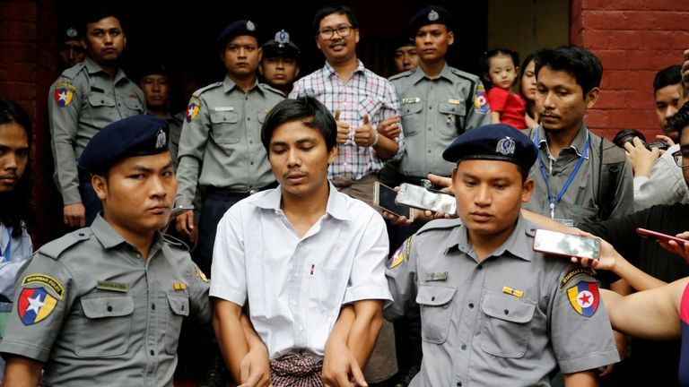 Detained Reuters journalist Kyaw Soe Oo and Wa Lone are escorted by police as they leave after a court hearing in Yangon, Myanmar