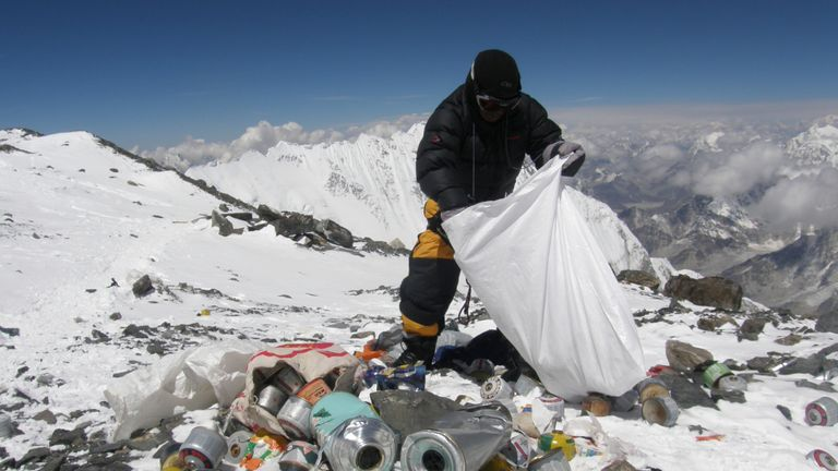 A Nepalese sherpa collecting garbage, left by climbers