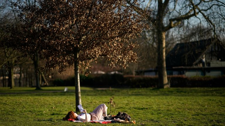 A woman lounges with a book in Regent's Park