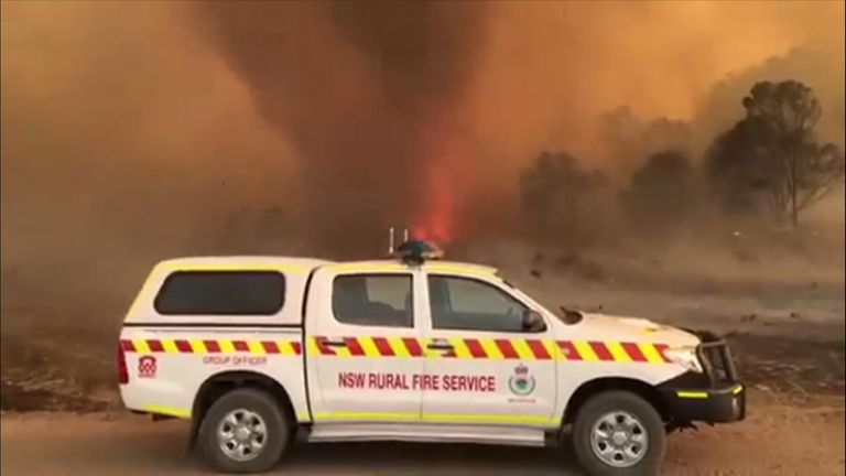 A fiery whirlwind swung past firefighters patrolling an out-of-control blaze at Wallangarra, Queensland.