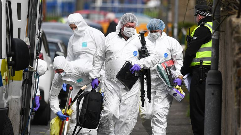 Forensic officers examine a crime scene in Govan after the death of Julie Reilly