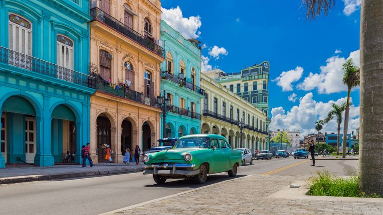 Cityscape with american green Chevrolet classic car on the main street in Havana City Cuba