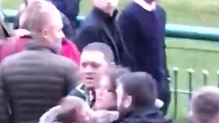 A woman clutching a small child being led away from the scene of a brawl at a Haydock races