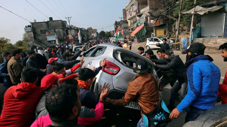 Demonstrators tried to tip over a car as chaos broke out following the attack