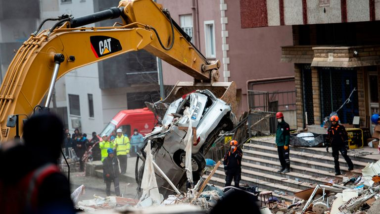 Rescue workers search the rubble of an eight-storey building after it collapsed