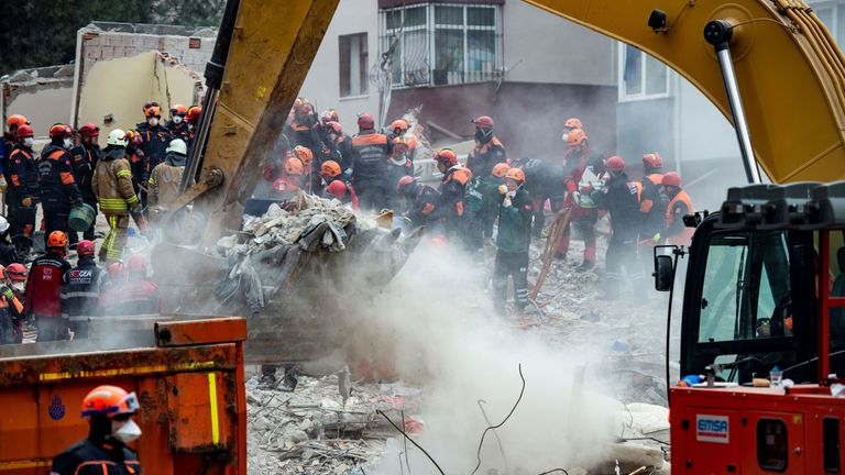 Rescue workers search the rubble of the building which collapsed in the Kartal district