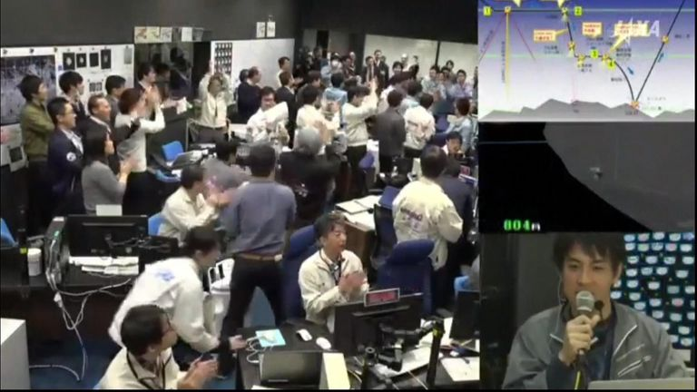 Workers celebrate the spacecraft's landing