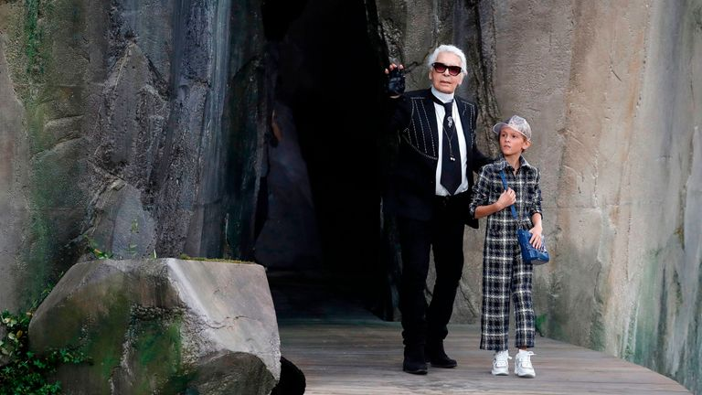 The fashion designer walks with his godson Hudson Kroenig during a 2018 Chanel show