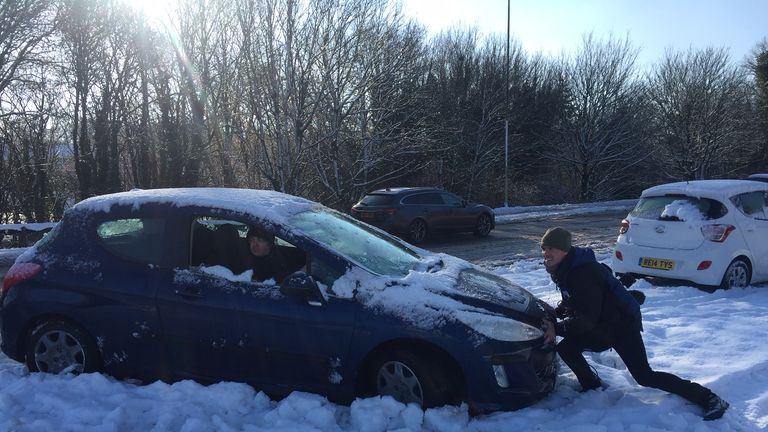People work to free their cars trapped by heavy snow near the M3 in Basingstoke