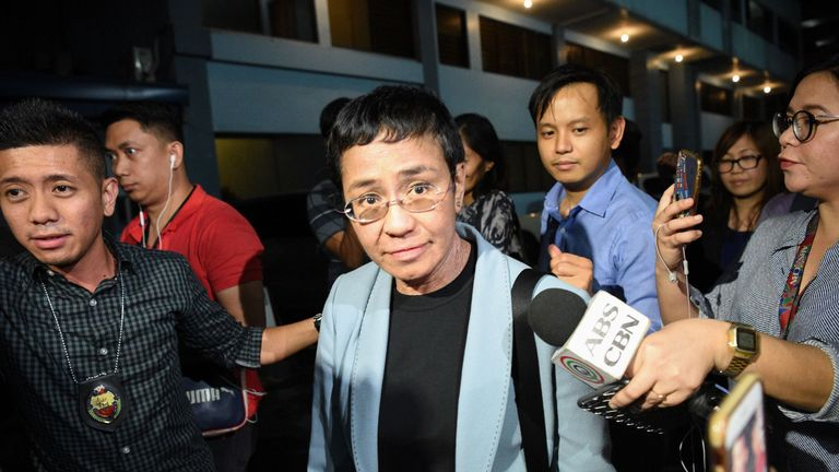 Maria Ressa escorted by a National Bureau Investigation (NBI) agent (L) at the NBI headquarters after her latest arrest in Manila