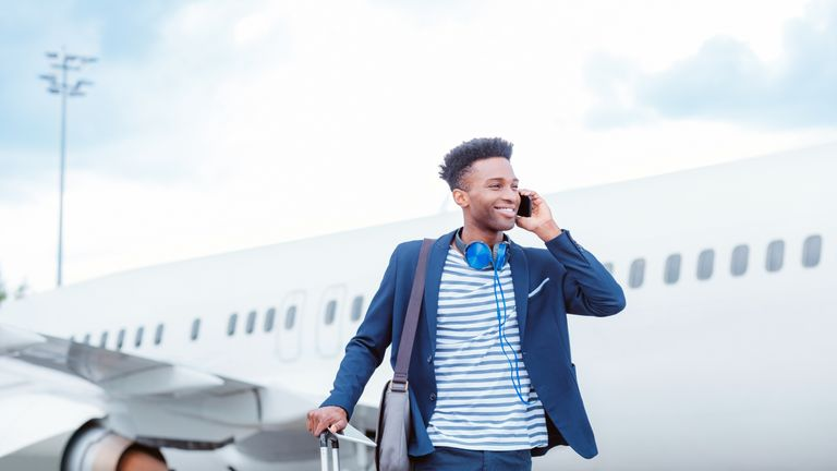 Young businessman talking on smart phone in front of airplane - Stock image