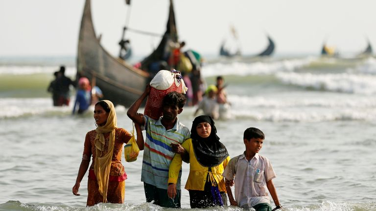 Rohingya refugees walk to the shore with his belongings after crossing the Bangladesh-Myanmar border by boat through the Bay of Bengal in Teknaf, Bangladesh