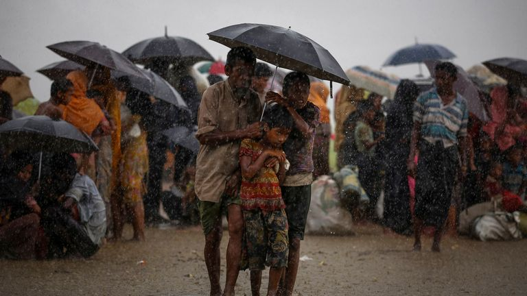 Rohingya refugees try to take shelter from torrential rain as they are held by the Border Guard Bangladesh (BGB) after illegally crossing the border, in Teknaf, Bangladesh