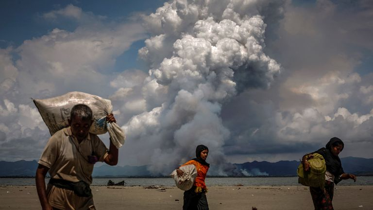 Smoke is seen on the Myanmar border as Rohingya refugees walk on the shore after crossing the Bangladesh-Myanmar border by boat through the Bay of Bengal, in Shah Porir Dwip, Bangladesh