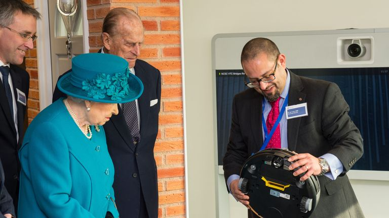LONDON, ENGLAND - FEBRUARY 14: Technical Director Dr Ian Levy (R) shows Queen Elizabeth II and the Prince Philip, Duke of Edinburgh a robot vacuum cleaner which could be vulnerable to cyber attack during a visit to attend the official open the National Cyber Security Centre on February 14, 2017 in London, England. The National Cyber Security Centre (NCSC) is designed to improve Britain's fight against cyber attacks and act as an operational nerve centre. (Photo by Dominic Lipinski - WPA Pool/Get