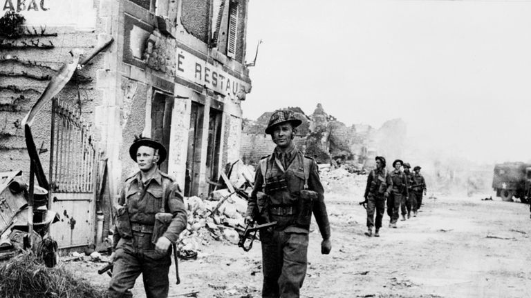 British soldiers walk through the village of Douet after the June 1944 Normandy landings