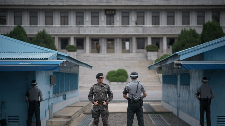 Soldiers stand guard before the demarcation line separating North and South Korea in the DMZ