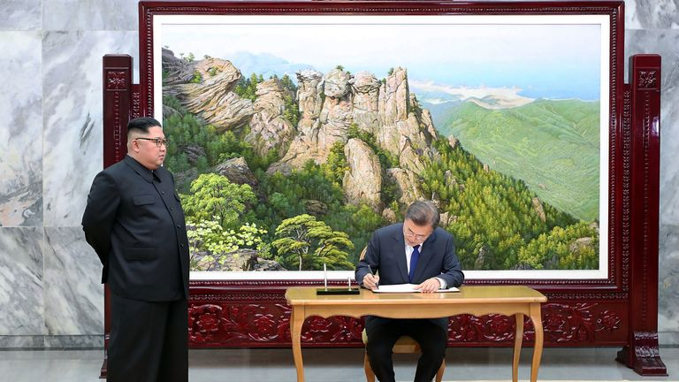 South Korean President Moon Jae-In signs his name as North Korean leader Kim Jong-Un stands before a meeting in Panmunjom, North Korea