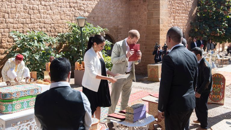 The royals look at items from a merchant in the walled public Andalusian Gardens