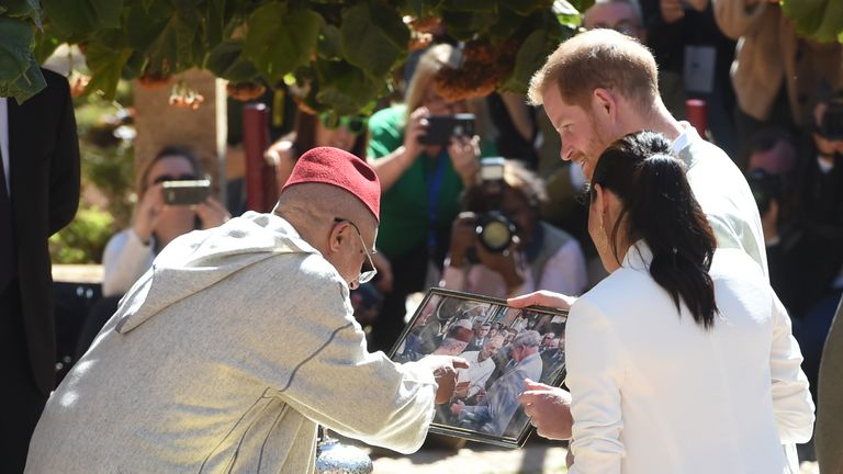 Harry and Meghan speak to a merchant as they view a picture of Prince Charles, Prince of Wales