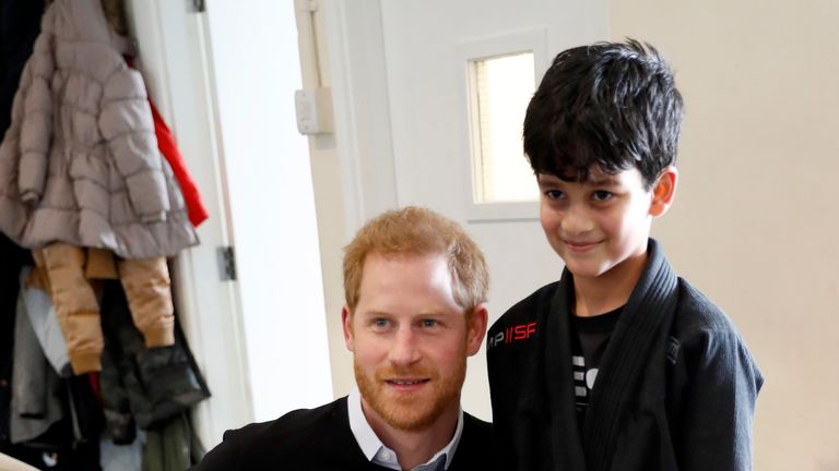Prince Harry posed with a child and his teddy present at the youth centre