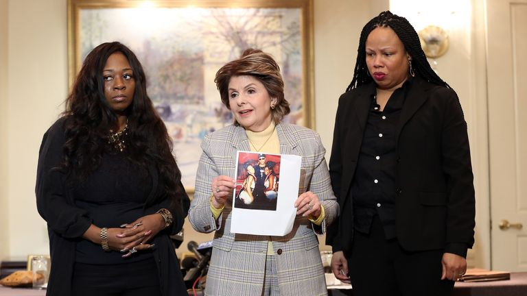 Rochelle Washington, left, attorney Gloria Allred and Latresa Scaff display photos of the night they claim they were abused