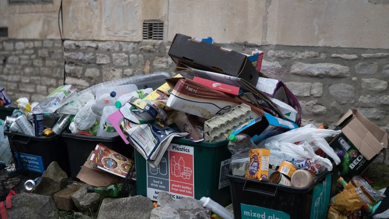 Rubbish in bins and recycling in boxes wait to be collected outside a residential property