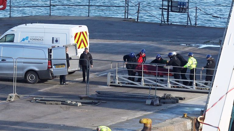 A stretcher carrying a body is removed from the Geo Ocean III specialist search vessel docked in Portland, Dorset