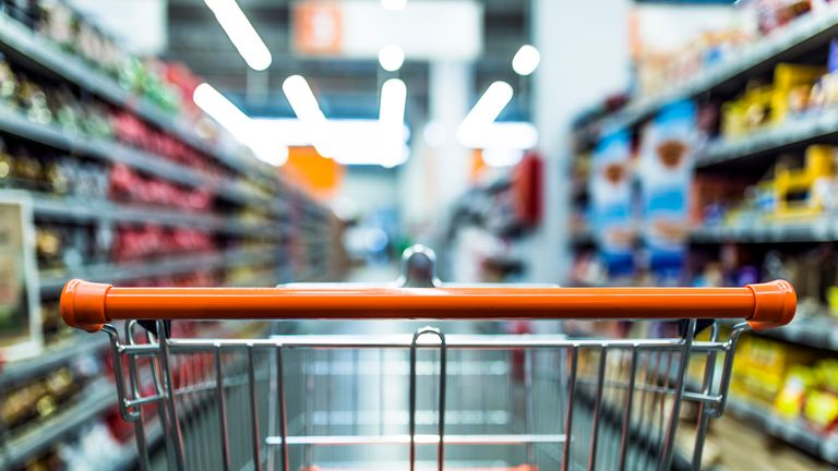 Abstract blurred photo of store with trolley in department store bokeh background. Supermarket aisle with empty red shopping cart (Abstract blurred photo of store with trolley in department store bokeh background. Supermarket aisle with empty red shop