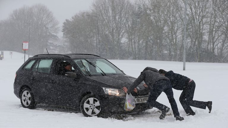 Two men help a driver try to get his car moving, after snowfall
