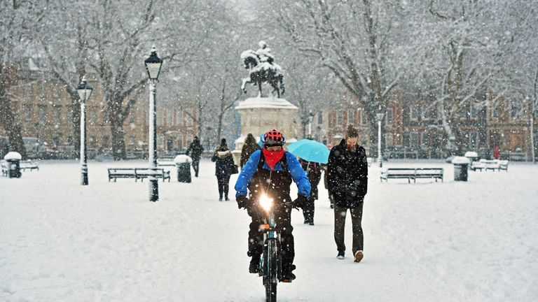 A cyclist rides through Queen's Square in Bristol in heavy snow