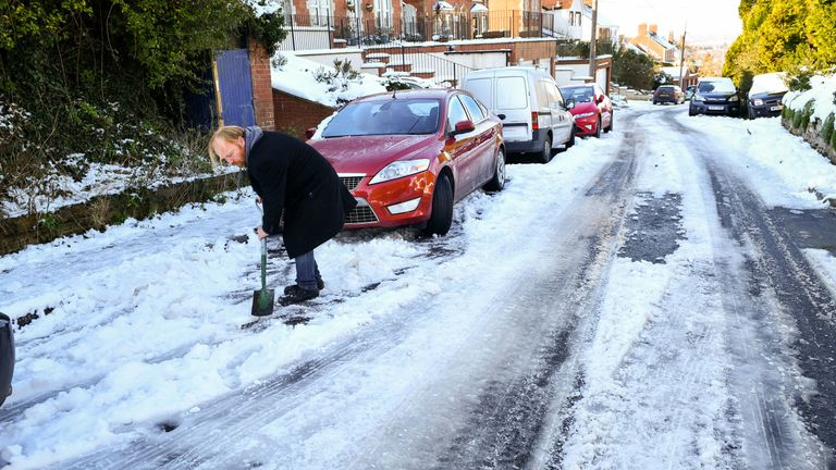 A man clears snow to try free his car in Wiltshire