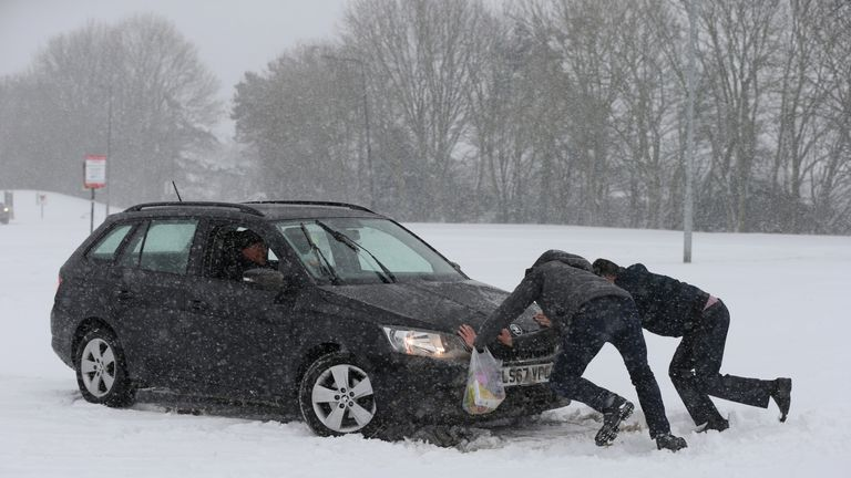 Two men appeared to help stuck motorist as snow fell across the country