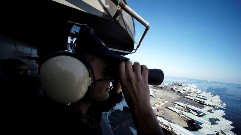 December: A US sailor keeps watch as the USS John C Stennis  makes its way through the Strait of Hormuz