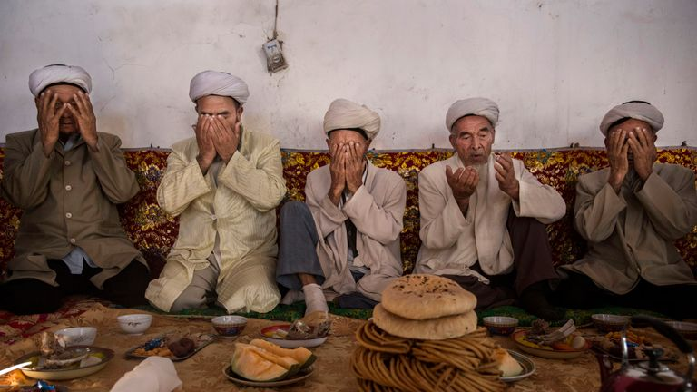 Uighur men pray in Turpan, China