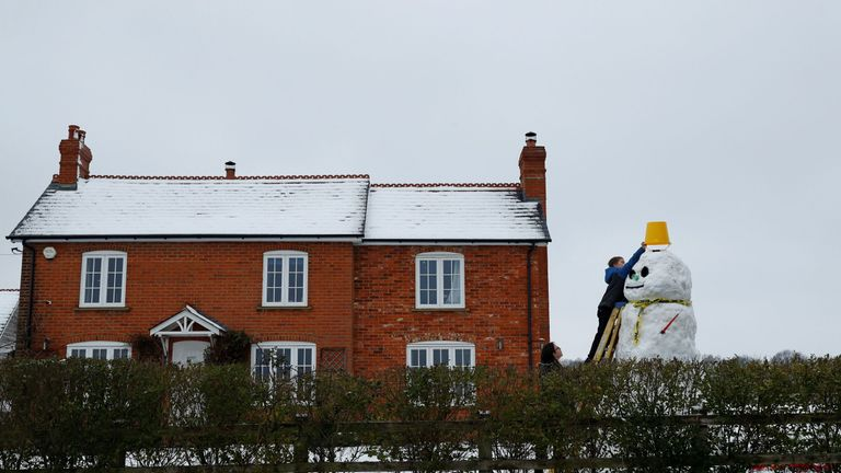 A boy puts a bucket for a hat onto the top of a snowman near Hartley Wintney, in Hampshire