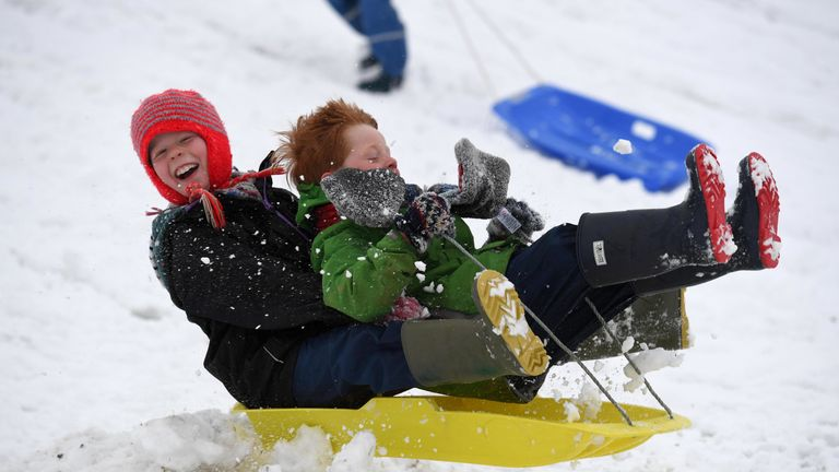 Children enjoy a day off school with some sledging at The Great Field in Poundbury