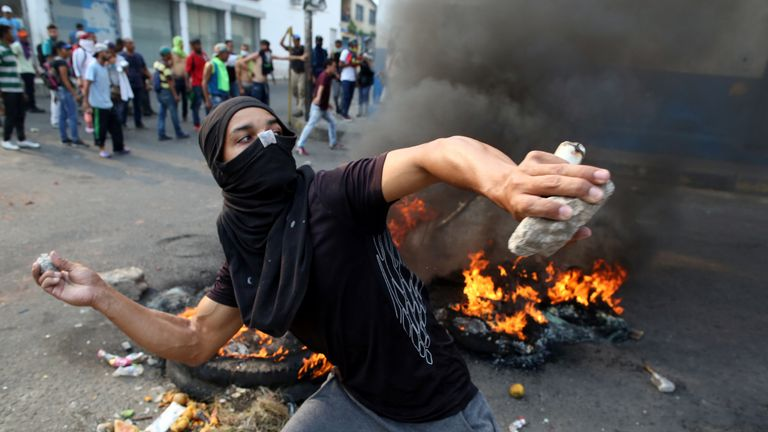 A protester throws an object at Venezuelan security forces