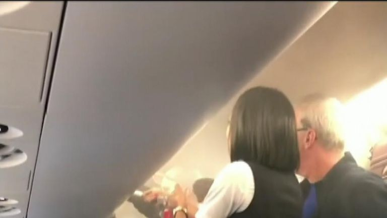 Cabin crew extinguish a fire on a plane caused by an electric cigarette product