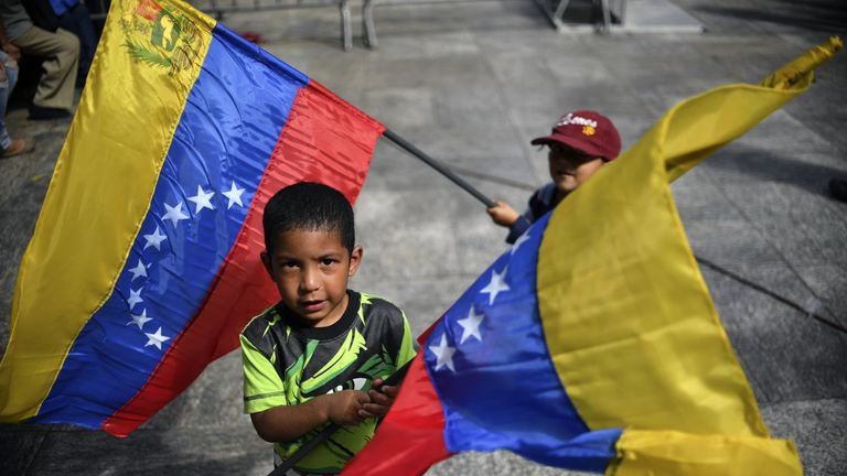 Children wave Venezuelan national flags, as supporters of Venezuelan President Nicolas Maduro gather at Bolivar square in Caracas