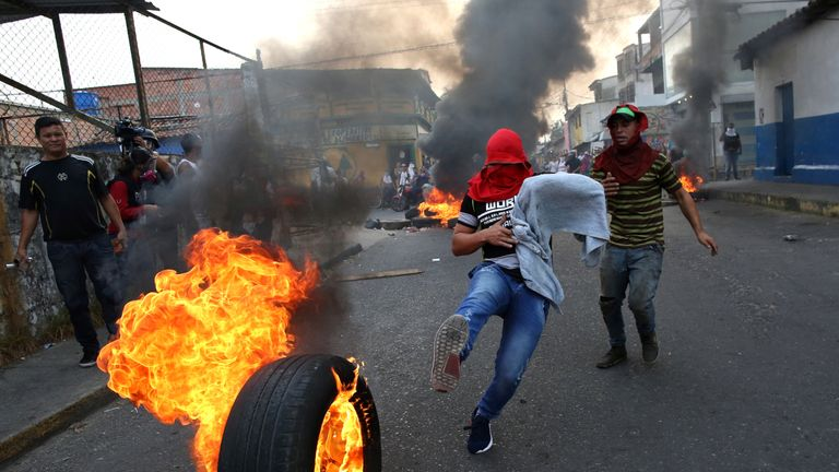 A demonstrator kicks a burning tyre in Urena