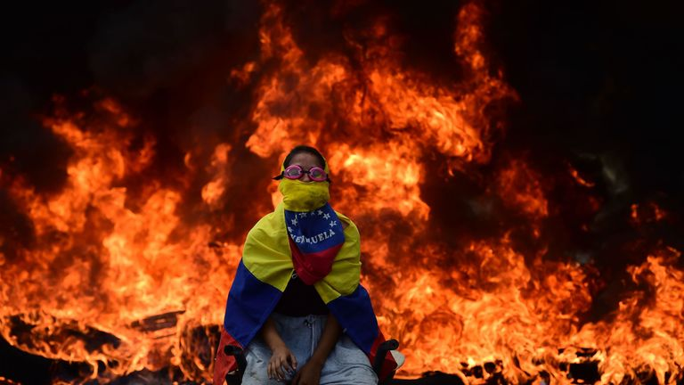 A Venezuelan opposition activist sits in front of a burning barricade