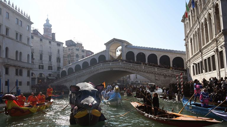 Spectators watch from the Rialto Bridge during the carnival in Venice