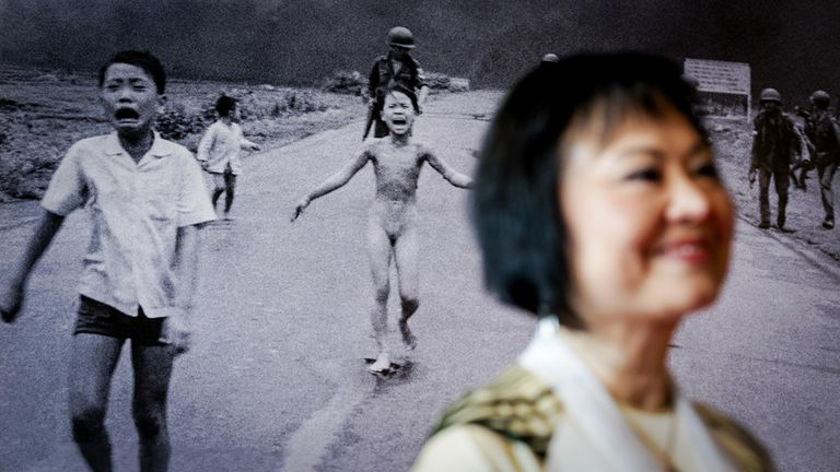 Vietnam war survivor Kim Phuc Phan Thi in front of the photo for which she is known