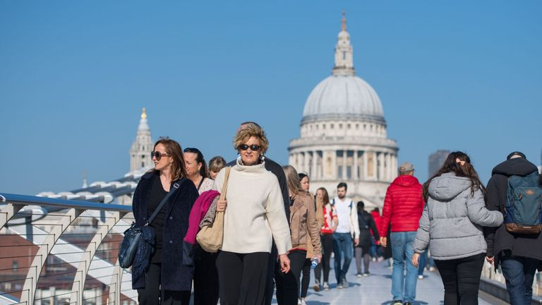 People enjoy the mild weather as they cross London's Millennium Bridge in central London