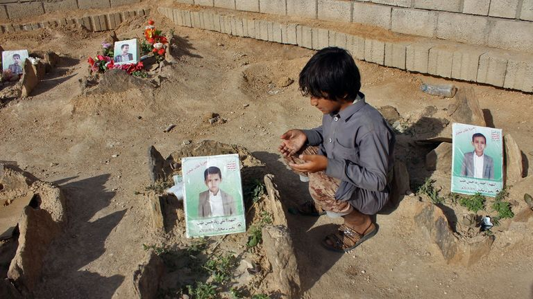 A Yemeni child recites a prayer by the graves of schoolboys who were killed while on a bus that was hit by a Saudi-led coalition air strike