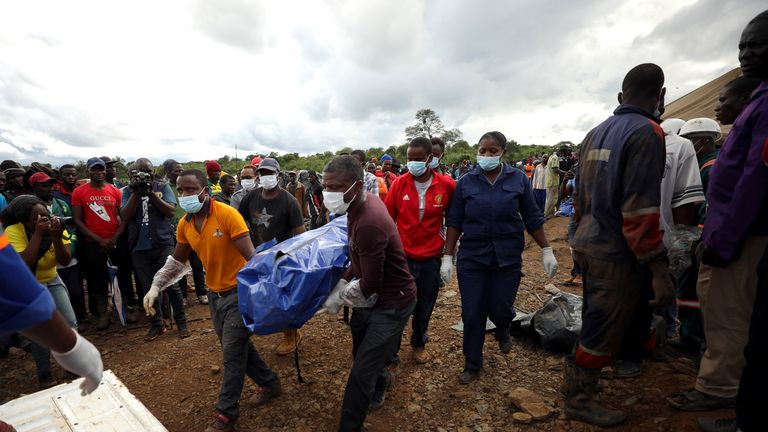 A body bag is taken to a tent for identification