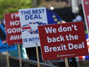 Brexit placards are lined up on railings outside the Houses of Parliament in London