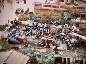 People gather on the roof of a house submerged by floods in Buzi o