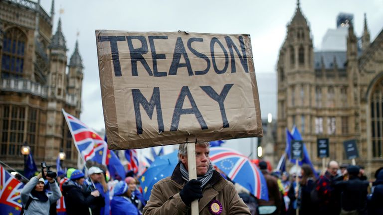 """A pro-Brexit protester holds a banner as anti-Brexit protesters demonstrate outside the Houses of Parliament, ahead of a vote on Prime Minister Theresa May's Brexit deal, in London, Britain, January 15, 2019. To match package """"BRITAIN-EU/TIMELINE"""" REUTERS/Henry Nicholls /File Photo"""
